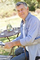 Portrait of smiling senior man reading newspaper at table in garden