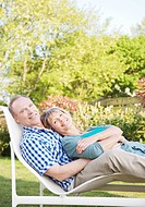 Portrait of smiling senior couple laying in lounge chair in backyard