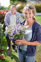 Portrait of smiling woman holding potted flower in garden