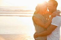 Serene couple hugging on beach at sunset