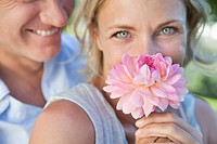 Close up of woman smelling pink flower