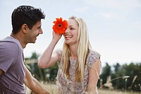 Smiling woman holding flower over eye and looking at man in rural field