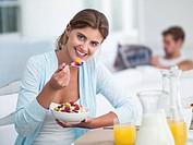 Portrait of smiling woman eating fruit salad