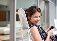 Smiling woman using cell phone on sunny patio