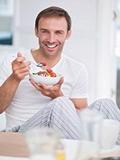 Portrait of smiling man eating fruit salad in pajamas