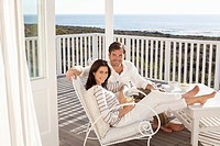 Portrait of smiling couple relaxing on patio overlooking ocean