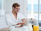 Smiling man reading newspaper and drinking coffee in bathrobe at breakfast table
