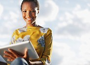 Portrait of smiling businesswoman using digital tablet under blue sky with clouds