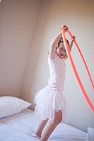 Girl playing with hula hoop in bedroom