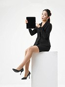 Portrait of Business woman sitting on white stool useing tablet PC