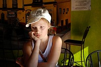 Young girl with hat wating for fod at a restaurant, Nogales, Mexico