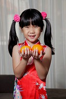 Young Chinese girl holding oranges for Chinese New Year