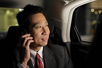 Mature man sitting in the back of a car talking on the phone