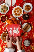 Hands holding red envelopes Hong Bao over table with Chinese food.