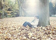 Boy sitting under tree in autumn leaves, portrait