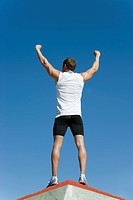 Male athlete standing on winner´s podium with arms raised in victory, rear view