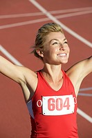 Woman running on track with arms raised in victory