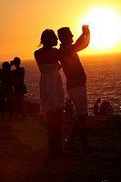 COUPLE TAKING PICTURES DURING THE SUNSET, MIKONOS, GREECE