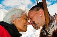 A Maori man with ta moko facial tattoo and an elderly Maori woman doing hongi traditional Maori greeting , Te Puia New Zealand Maori Arts & Crafts Ins...