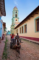 Two men on horse_drawn cart travelling along a quiet street in Trinidad, Sancti Spiritus Province, Cuba, West Indies, Caribbean, Central America