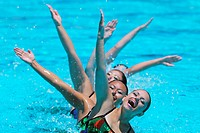 Group of Synchronized Swimmers Performing in Swimming Pool