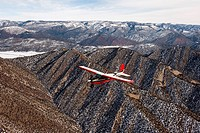 A red and white plane flies over snow dusted Colorado mountains.