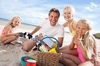Portrait of smiling family with dog picnicking on sunny beach