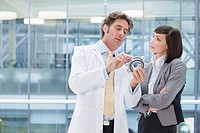 Engineer in lab coat and businesswoman examining part in office