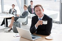 Portrait of smiling businessman drinking coffee and using laptop