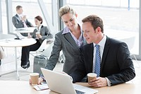 Businessman and businesswoman drinking coffee and using laptop