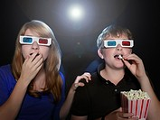 Boy and girl watching 3_D movie eating popcorn