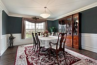 Dining room in luxury home with dark teal walls