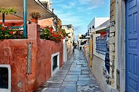 Path with colorful buildings along the main route in the village of Oia in Santorini, Greece