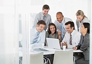 Business people laughing while looking at laptop
