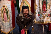 A pilgrim poses with banners with the image of Our Lady of Guadalupe virgin enter Our Lady of Guadalupe Basilica in Mexico City, December 9, 2011  Hun...
