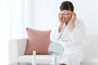 Middle_Aged Woman Wearing Bathrobe Using Skin Care Product
