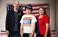 Smiling Hispanic family standing in polling place