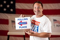 Mixed race man holding direction sign in polling place