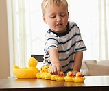 Caucasian boy playing with rubber ducks