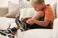 Caucasian boy tying shoes