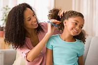 Mixed race mother brushing daughter´s hair