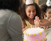 Mixed race mother bringing daughter a birthday cake