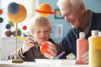 Caucasian man helping grandson with science project
