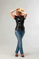blonde woman in a leather vest and jeans