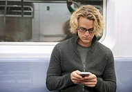 Caucasian man text messaging on cell phone on subway train