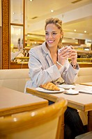 Hispanic woman having breakfast in cafe