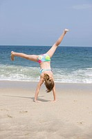 Caucasian girl doing cartwheel on beach