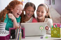 Laughing girls using laptop together