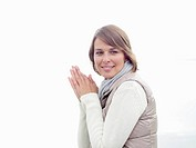 Germany, Munich, Mature woman in warm clothing with hands clasped, smiling