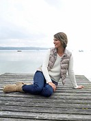 Germany, Munich, Mature woman sitting on jetty near lake, smiling